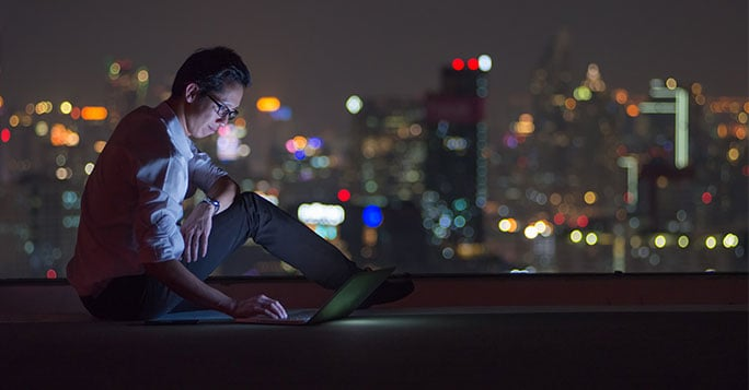 woman using laptop on a rooftop